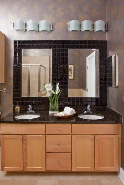 I removed the standard one large frameless mirror and installed 2 black tiled mirrors, modern lighting, and wallpaper to update his bathroom.