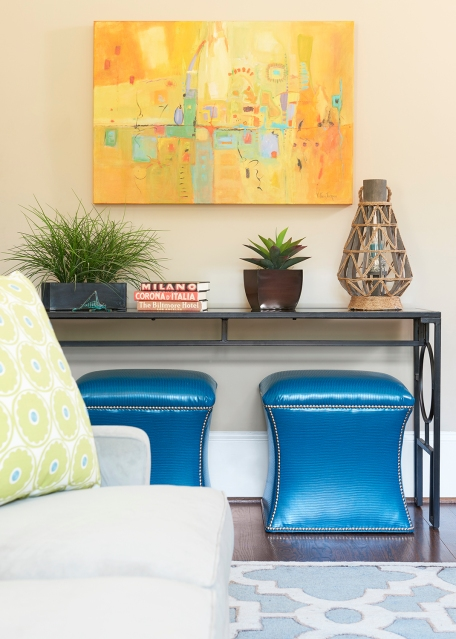 The side wall comes alive with colorful art, glass top iron console and these teal blue faux leathered stools.